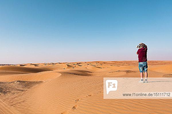 Älterer Mann beim Fotografieren der Wüste,  Wahiba Sands,  Oman
