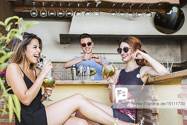 Two happy women having a drink at a bar