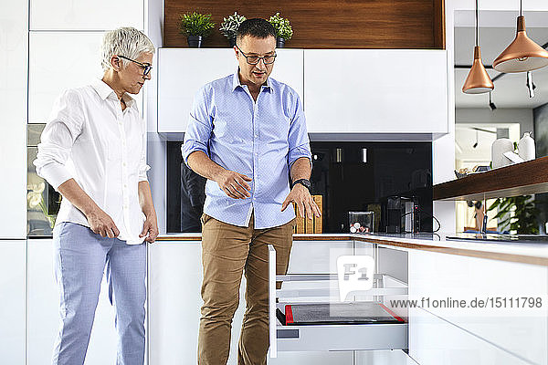 Man and mature woman talking in a kitchen retail store