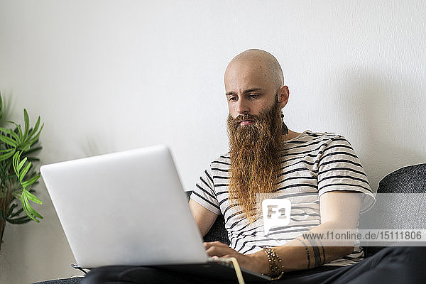 Portrait of hipster using laptop at home