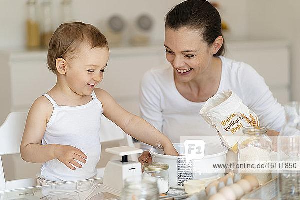 Glückliche Mutter und kleine Tochter backen zu Hause in der Küche gemeinsam einen Kuchen
