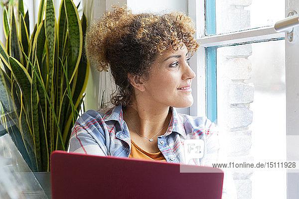 Frau mit Laptop schaut im Büro aus dem Fenster