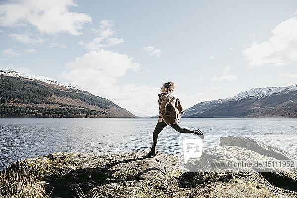 UK  Scotland  young woman running at Loch Lomond