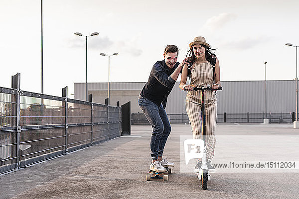 Young man and woman riding on longboard and electric scooter on parking deck