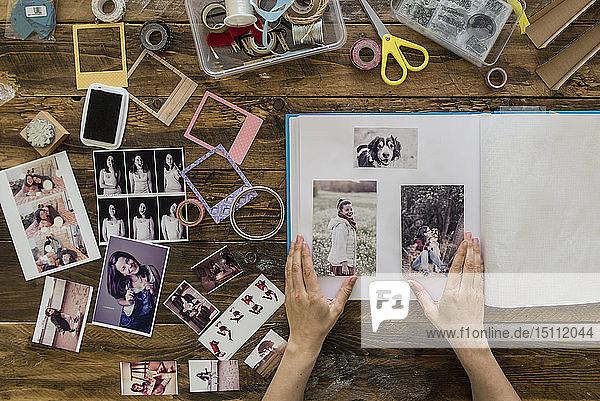 Draufsicht auf die Hände der Frau beim Gestalten des Fotoalbums