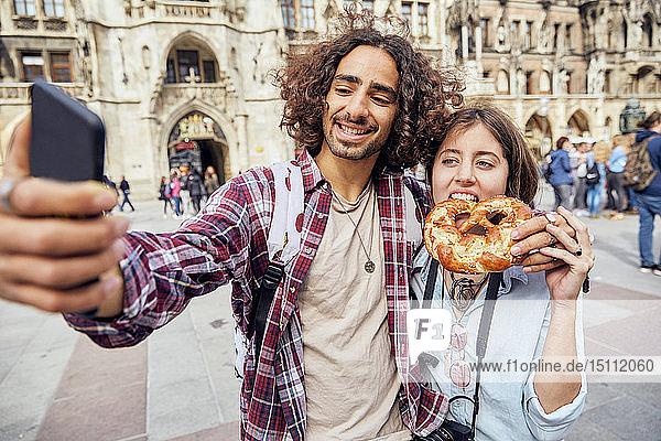 Junges Paar bei einem Selbstmord mit Brezel im Mund  München  Deutschland