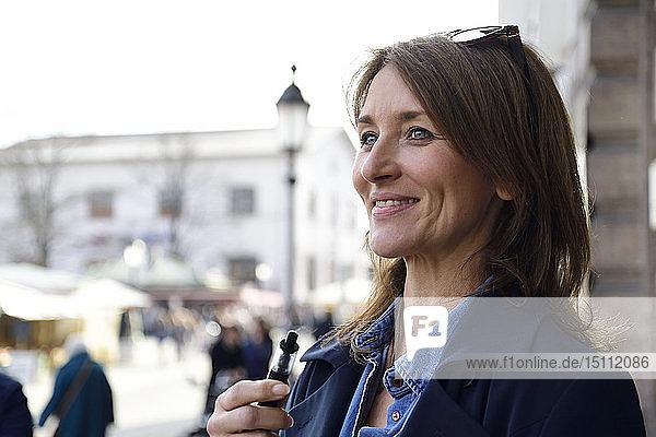 Reife Frau raucht elektronische Zigarette in der Stadt