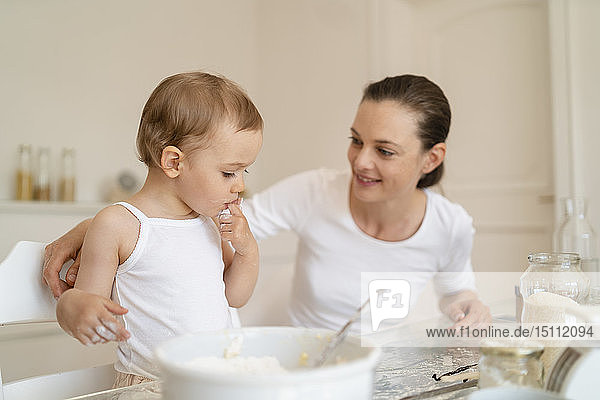 Mutter und kleine Tochter backen zu Hause in der Küche gemeinsam einen Kuchen
