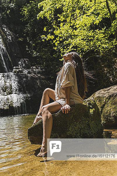 Junge Frau sitzt auf einem Felsen an einem Wasserfall  Garrotxa  Spanien
