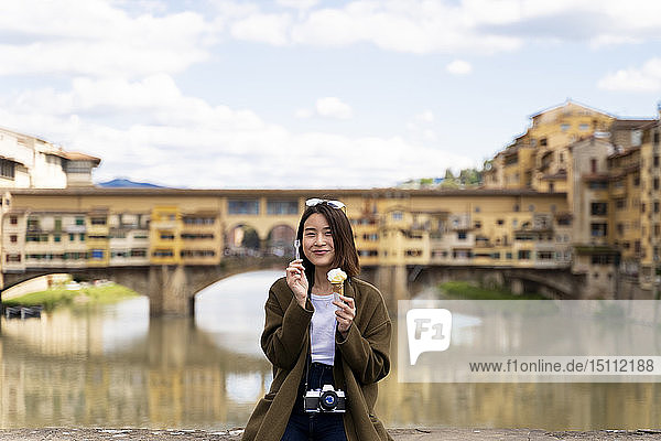 Italy  Florence  young tourist woman eating an ice cream cone at at Ponte Vecchio