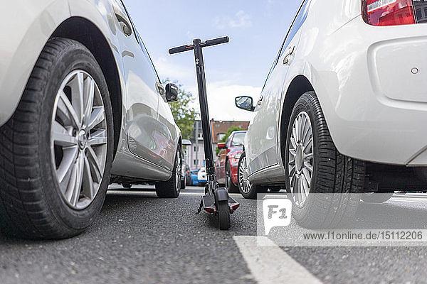 E-Scooter zwischen zwei Autos auf Parkplatz geparkt