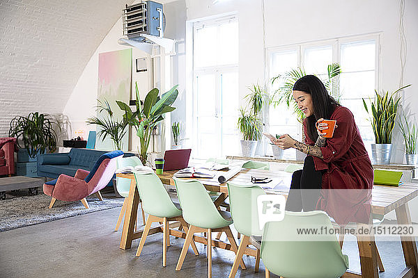 Smiling woman using cell phone in modern office