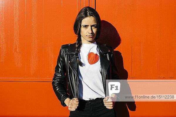 Junge Frau auf einer roten Wand im Hintergrund