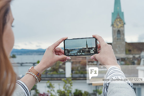 Young woman taking smartphone picture in the city  Zurich  Switzerland