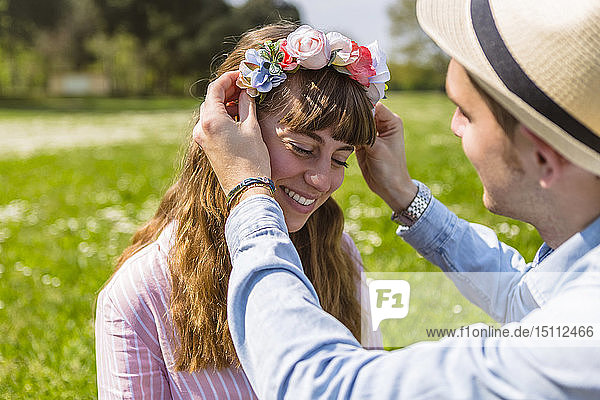 Young man putting flowers on on his girlfriend's head