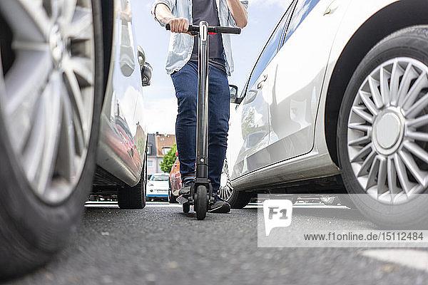 Mann mit E-Scooter zwischen zwei Autos  Teilansicht