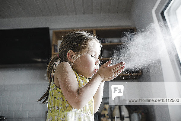 Little girl blowing flour in the air in the kitchen
