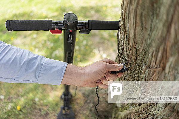 Mann hält den Stecker des E-Scooters in der Hand vor dem Baumstamm  Nahaufnahme