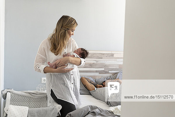 Mother holding her newborn baby in bedroom with father sleeping in background