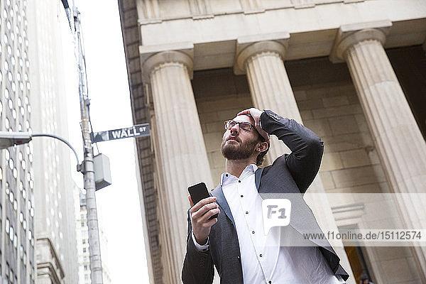 Porträt eines besorgten jungen Geschäftsmannes mit Handy vor der Börse  New York City  USA