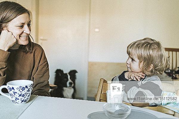 Lächelnde Mutter und Tochter sitzen zu Hause am Tisch mit Hund im Hintergrund