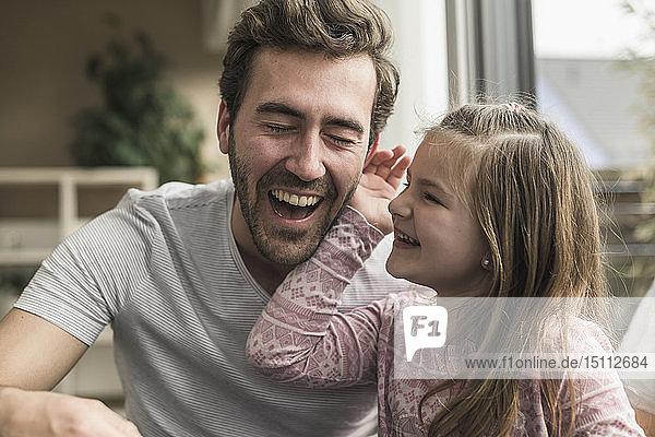 Kleines Mädchen streichelt lachend die Wange eines Mannes
