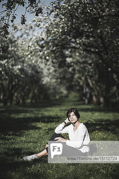 Frau sitzt auf Wiese zwischen Apfelbäumen