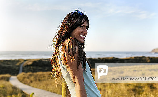 Portrait of a smiling woman in dunes at sunset