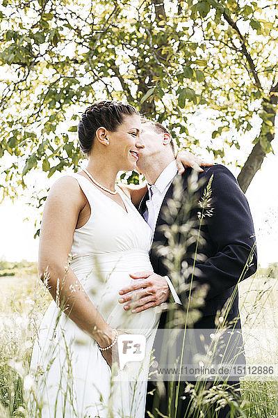 Schwangere Braut mit ihrem Ehemann hält Babybauch auf einer Wiese