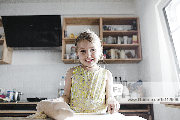Portrait of smiling little girl rolling out dough in the kitchen