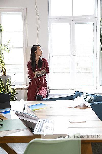 Frau schaut im Amt aus dem Fenster