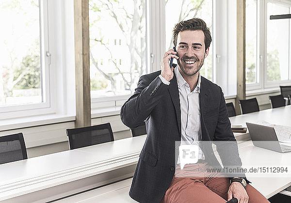 Junger Geschäftsmann sitzt im Sitzungssaal und telefoniert