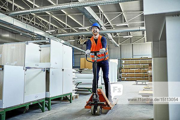 Lachender Arbeiter auf Palettenhubwagen in der Fabrik