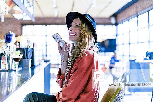 Lächelnde Frau mit Smartphone in einem Café