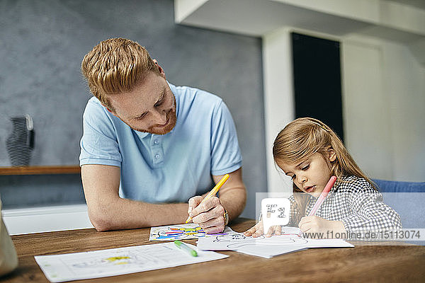 Father and daughter sitting at table  painting colouring book