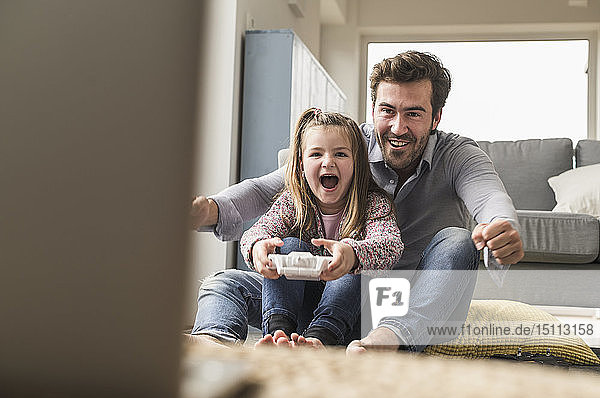 Young man and little girl playing computer game with gaming console