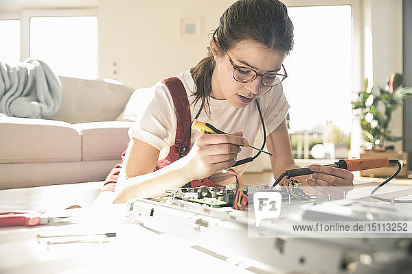 Young woman working on computer equipment at home