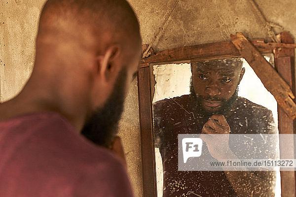 Mosambik  Maputo  junger Mann  der sein Spiegelbild betrachtet
