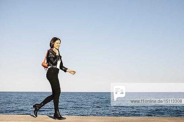Glückliche Frau mit roter Tasche beim Gehen  das Meer im Hintergrund