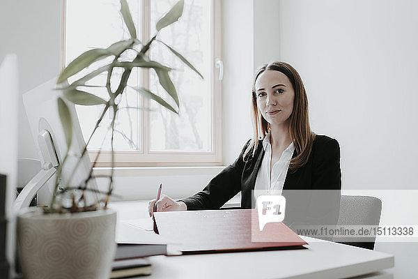 Porträt einer selbstbewussten jungen Frau  die am Schreibtisch im Büro arbeitet