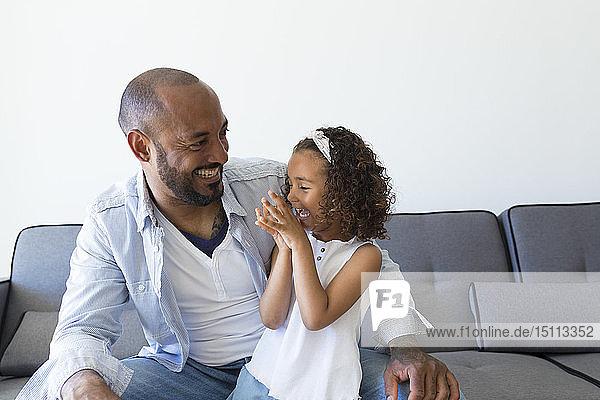 Glücklicher Vater und Tochter sitzen zu Hause auf der Couch