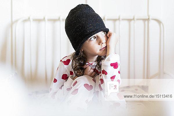 Porträt eines tagträumenden kleinen Mädchens,  das mit Mütze und Pyjama im Bett sitzt