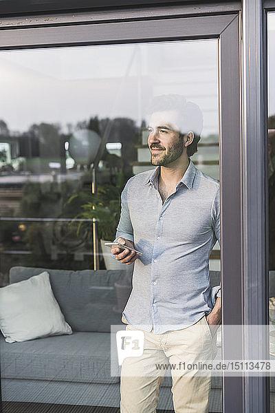 Junger Mann schaut aus dem Fenster und benutzt ein Smartphone