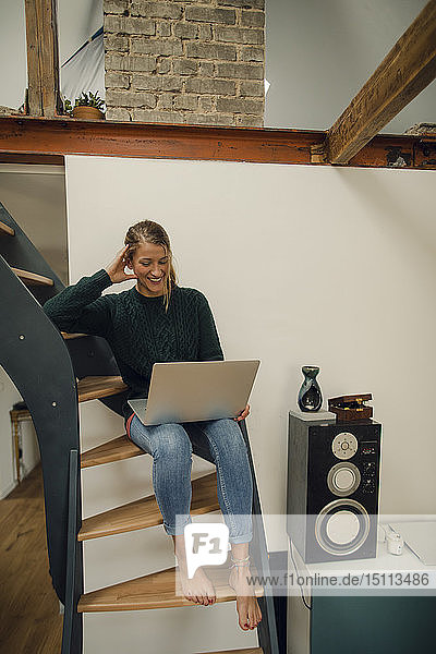 Smiling young woman sitting on stairs at home using laptop