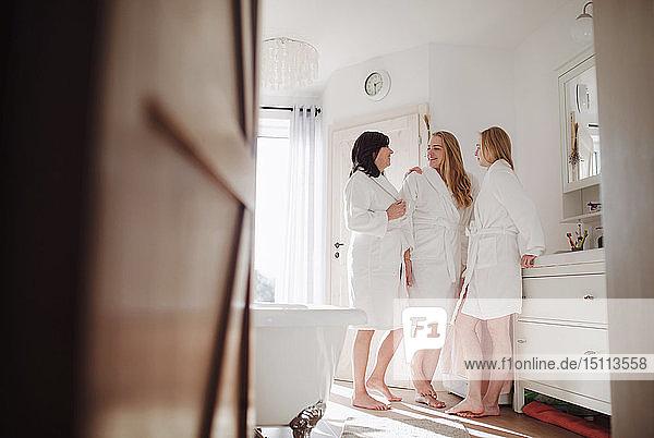 Glückliche reife Frau mit zwei Töchtern in einem Badezimmer zu Hause