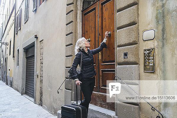 Italien  Florenz  reife Frau in Schwarz gekleidet  steht mit rollendem Koffer vor der Eingangstür