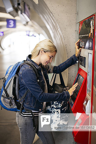 Smiling woman using ticket machine at the station
