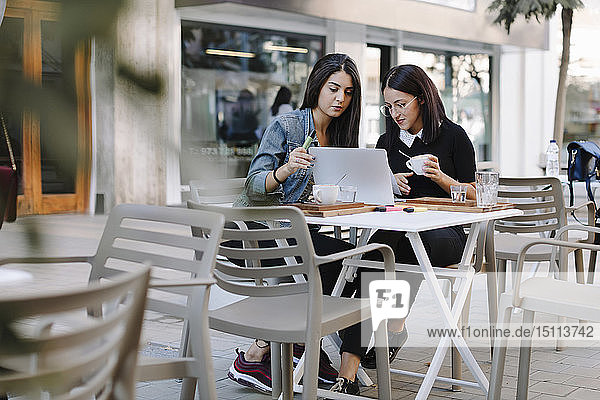 Two friends sitting together at a pavement cafe using laptop