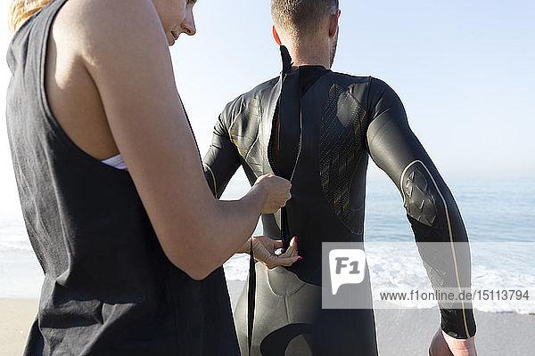 Frau  die den Neoprenanzug des Mannes am Strand zumacht