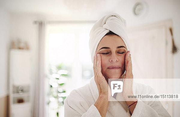 Porträt einer reifen Frau in einem Badezimmer zu Hause  die Feuchtigkeitscreme aufträgt